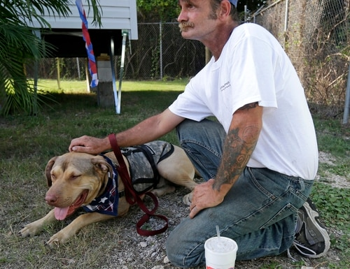 Army veteran Jerry Lambert pets his service dog Sam before a ribbon-cutting ceremony for Companions for Life Training Academy, a Veterans Service Dog Training Program & Facility, at the Jefferson Parish Animal Shelter in Harahan, La., Friday, Sept. 25, 2015. Veterans will learn to train service dogs and to teach other military veterans suffering from PTSD, brain injury or other medical problems how to train their own pets to meet their medical or psychological needs. They will be among the first participants in the program to teach veterans, including those who've never worked with canines, to train their own service dogs: animals coming from shelters. (AP Photo/Gerald Herbert)