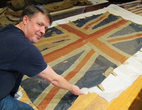 In this Thursday, Dec. 7, 2017, photo, Charles Swift, managing director and curator of the U.S. Naval Academy Museum in Annapolis, Md., looks up from a British flag of the HMS Landrail, which was captured in 1814 by American privateers sailing in the English Channel. It is one of 61 flags recently removed from glass cases at the U.S. Naval Academy for preservation. (Brian Witte/AP)