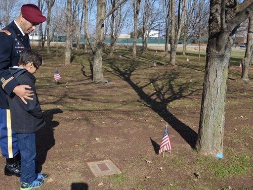 Chief Warrant Officer 2 Mickael Cruz of the 160th Special Operations Aviation Regiment, and his son, Joshua, visit the memorial tree for Cruz's father at Fort Campbell, Kentucky, in December 2014. Cruz's father, Staff Sgt. Francisco Cruz Salgado, was among 248 soldiers who lost their lives in a plane crash in Gander, Newfoundland, Dec. 12, 1985, while returning home from a peacekeeping mission in Egypt. Cruz, now a CWO3, says the commemoration each year is a time to reconnect with families and friends of those who were lost in the crash. (Sgt. 1st Class Eric R. Abendroth/Army)