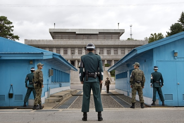 South Korean soldiers, foreground, look toward the North Korean side as a North Korean soldier approaches the UN truce village building that sits on the border of the Demilitarized Zone (DMZ), the military border separating the two Koreas, in Panmunjom, South Korea, on Sept. 30, 2013, during a visit by US Defense Secretary Chuck Hagel. (Jacquelyn Martin/AFP via Getty Images)