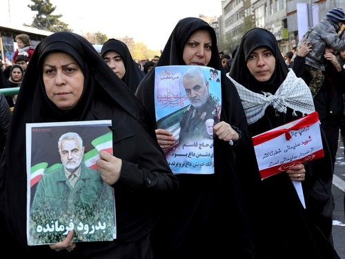 Mourners holding posters of Iranian Gen. Qassem Soleimani attend a funeral ceremony for him and his comrades at the Enqelab-e-Eslami (Islamic Revolution) Square in Tehran, on Jan. 6. (Ebrahim Noroozi/AP)