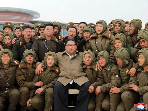 In this undated photo provided on Monday, Nov. 18, 2019, by the North Korean government, North Korean leader Kim Jong Un, center, poses with North Korean air force sharpshooters and soldiers for a photo at an unknown location in North Korea. (Korean Central News Agency/Korea News Service via AP)