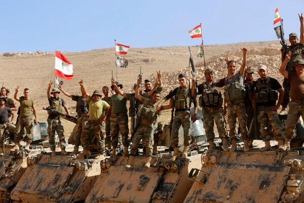 Lebanese army soldiers flash victory signs as they rest on top of an armored personnel carrier during a media trip organized by the Lebanese army, on the outskirts of Ras Baalbek, northeast Lebanon, Monday, Aug. 28, 2017. Lebanon's Hezbollah TV is reporting that Islamic State militants started leaving the border area with Syria on Monday as part of a negotiated deal to end the extremist group's presence there. (Hassan Ammar/AP)