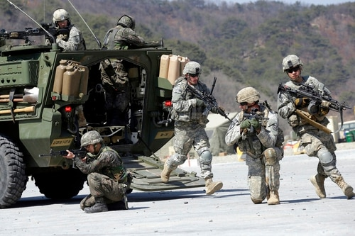 In this March 25, 2015, file photo, U.S. Army soldiers from the 25th Infantry Division's 2nd Stryker Brigade Combat Team and South Korean soldiers take their position during the annual joint military exercise Foal Eagle at the Rodriquez Multi-Purpose Range Complex in Pocheon, north of Seoul, South Korea. The Pentagon says the annual U.S.-South Korean military exercises that had been postponed for the Pyeongchang Winter Olympics will begin April 1. (ALee Jin-man/AP)
