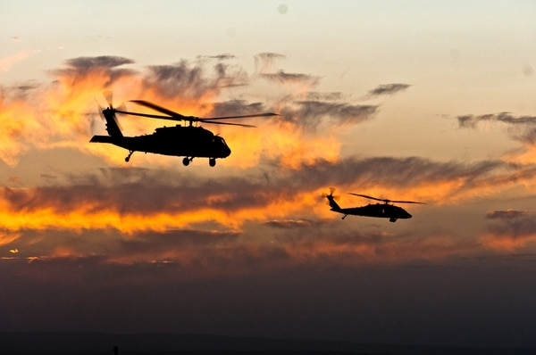 Two UH-60 Black Hawk helicopters hover over the skies of Spin Boldak, Afghanistan, on Dec, 24, 2011. A new coating Army researchers are working on could better protect helicopter rotor blades from sand particles. (Spc. Cory Sparks/Army)