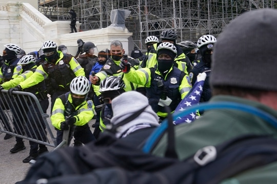 In this Jan. 6, 2021, photo, violent rioters try to break through a police line on the West Front of the Capitol, in Washington. (John Minchillo/AP)