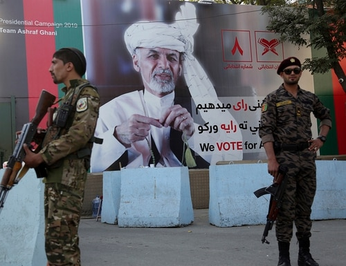 Afghan security forces stand guard in front of an election poster for presidential candidate Ashraf Ghani in Kabul, Afghanistan, on Sept. 23, 2019. (Rahmat Gul/AP)