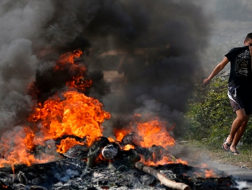 A Kosovo Albanian runs past a fire burning at a roadblock in Vojtesh, Kosovo, Sunday, Sept. 9, 2018. Kosovo Albanians burned tires and blocked roads with wooden logs, trucks and heavy machinery on a planned route by Serbia's President Aleksandar Vucic who was trying to reach the village of Banje while visiting Serbs in the former Serbian province. The Kosovo government is now working to establish a regular army. (AP Photo/Visar Kryeziu)