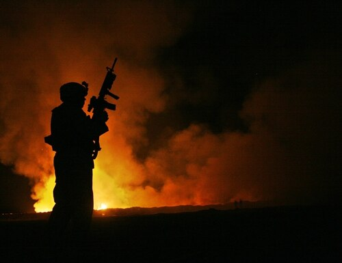 Sgt. Robert B. Brown, Fayetteville, N.C. with Regimental Combat Team 6, Combat Camera Unit watches over the civilian Fire Fighters at the burn pit as smoke and flames rise into the night sky behind him on May 25th, 2007. (Cpl. Samuel D. Corum/Marine Corps)