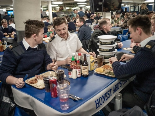 Royal Navy Engineering Technician Sam Ridgely (center) discussed their U.S. Navy Thanksgiving Dinner onboard the aircraft carrier Abraham Lincoln in Norfolk with fellow Royal Navy ET's Callum Squirrell (l) and Sam Prisk (r). (photo by Mark D. Faram/staff)