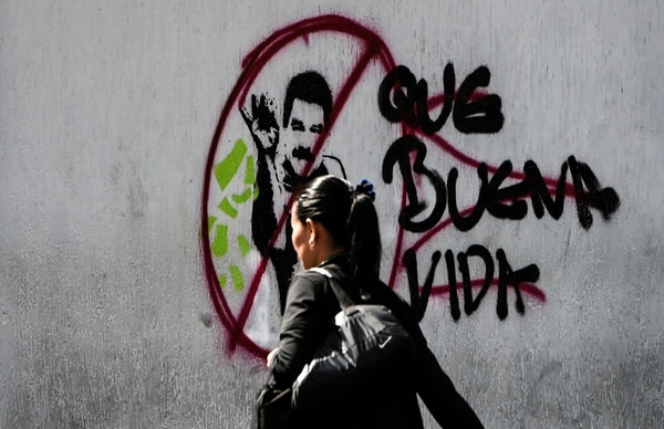 A woman walks past graffiti against Venezuelan President Nicolas Maduro in Caracas on Feb. 6, 2019. (Juan Barreto/ AFP via Getty Images)