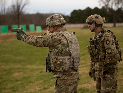 A soldier from the 101st Airborne Division, under the watchful eye of instructor Staff Sgt. Anthony Cirincione, learns how to fire the Army's new Modular Handgun System, or M17. The 101st Airborne, at Fort Campbell, Ky., was the first unit in the Army to receive the new handgun. (Daniel Woolfolk/Staff)