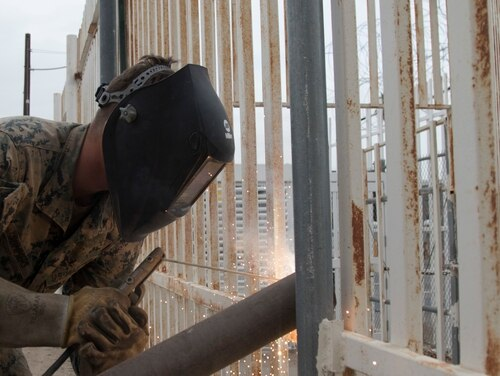 A Marine Corps engineer welds a wire support near the Andrade point of entry in California on Nov. 29, 2018. President Donald Trump signaled on Thursday he will declare a national emergency on border security in coming days, allowing him to divert billions of funds marked for military construction to his controversial southern wall project instead. (Staff Sgt. Jesse Untalan/Army)