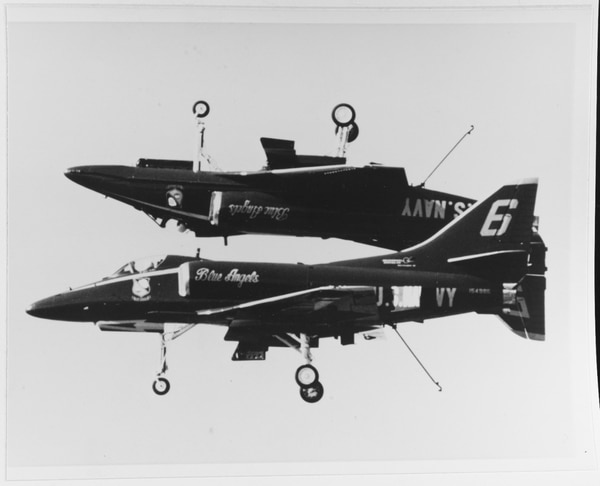 Two A-4F Skyhawks pass by in an upside-down formation, during a Blue Angels show. (National Archives)