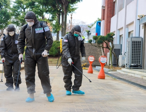 Two U.S. Army Soldiers and a Republic of Korea Army Soldier spray a COVID-19 infected area with a solution of disinfectant in Daegu, Republic of Korea, March 13, 2020. The Soldiers wear personal protective equipment with the primary function of protecting themselves from the disinfecting agent. (U.S. Army photo by Spc. Hayden Hallman, 20th Public Affairs Detachment)