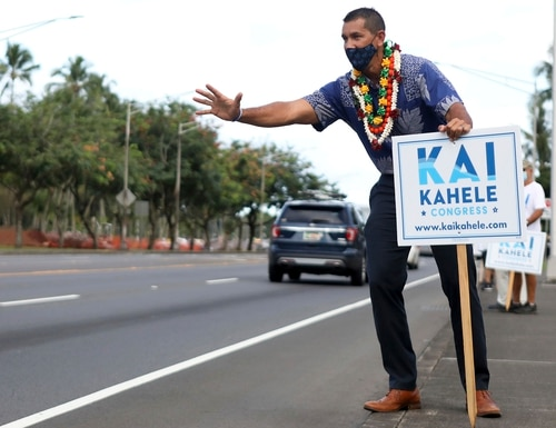 U.S. House of Representatives candidate Kai Kahele waves at people passing by while campaigning with supporters in Hilo, Hawaii, on Wednesday, Oct. 28, 2020. (Kelsey Walling/Hawaii Tribune-Herald via AP)