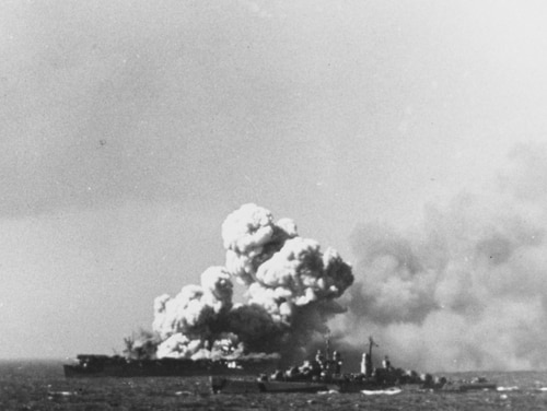 The light carrier Princeton (CVL-23) afire at about 1004 hours on 24 October 1944, soon after it was hit by a Japanese bomb during operations off the Philippines. This view shows smoke rising from the ship's second large explosion, as light cruiser Reno steams by in the foreground. (Photographed from the battleship South Dakota, now in the collections of the National Archives)