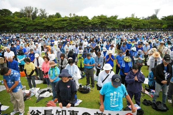 Protesters pay tribute to Okinawa Gov. Takeshi Onaga, who died last week, during a rally in Naha, Okinawa prefecture, southern Japan Saturday. Tens of thousands of protesters gathered in Okinawa vowing to stop a planned U.S military base relocation on the southern Japanese island. (Yohei Nishimura/Kyodo News via AP)