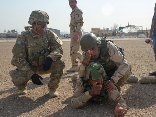 Iraqi Army soldiers secure an area during a assault an objective simulation while an infantryman with 2nd Battalion, 505th Parachute Infantry Regiment, 3rd Brigade Combat Team, 82nd Airborne Division, watches at Camp Taji, Iraq. The Army is looking for soldiers with experience training foreign forces. (Sgt. Cody Quinn/Army)