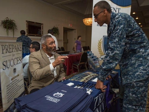 A university representative speaks with a sailor in 2016 about educational programs. (Navy photo)