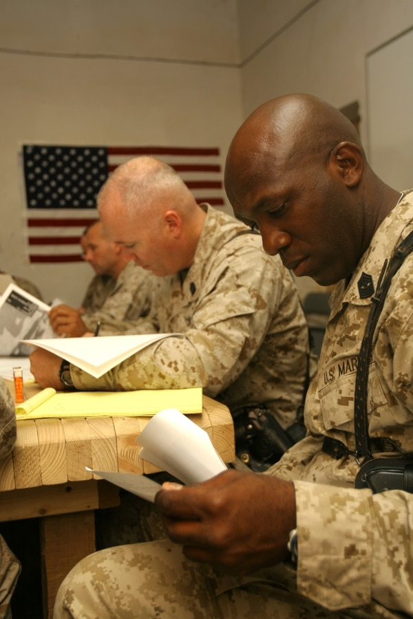 Sgt. Maj. Donald C. Miller (left) and Sgt. Maj. Ronald L. Green examine promotion packages during a combat meritorious promotion board at Al Taqaddum, Iraq, July 18. The board was composed of senior-enlisted Marines representing the subordinate squadrons in Marine Aircraft Group 16 (Reinforced), 3rd Marine Aircraft Wing (Forward). Miller is the squadron sergeant major for Marine Medium Helicopter Squadron 268, MAG-16, and a Lawrenceville, N.J., native. Green is the squadron sergeant major for Marine Light Attack Helicopter Squadron 169, MAG-16, and a Jackson, Miss., native.