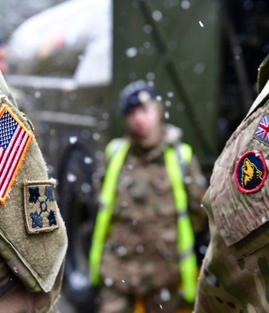 A British and an United States soldier stand side by side after a press conference on the military exercise Defender 2020 in Brueck, Germany, Wednesday, Feb. 26, 2020. (Soeren Stache/dpa via AP)