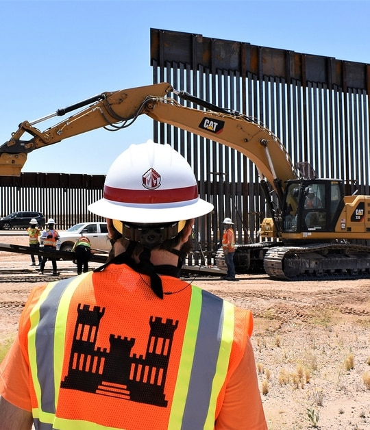 A U.S. Army Corps of Engineers South Pacific Border District employee views panel installation at the Yuma 2 border barrier project near Yuma, Ariz., May 21, 2020. (Robert DeDeaux/Army Corps of Engineers)