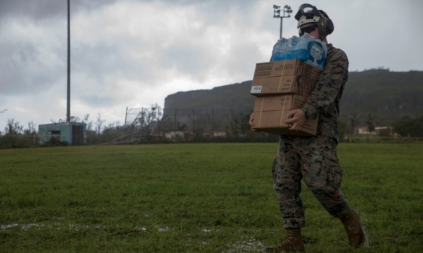 Marine Sgt. Andrew Fredley, a landing support specialist with Combat Logistics Battalion 31, carries food and water delivered by the