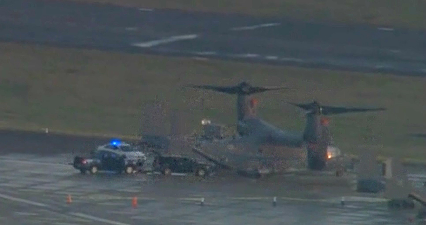 Aerial footage aired by the BBC showed a vehicle behind an Osprey on the flightline at RAF Mildenhall in England, surrounded by police. (Screenshot via BBC)