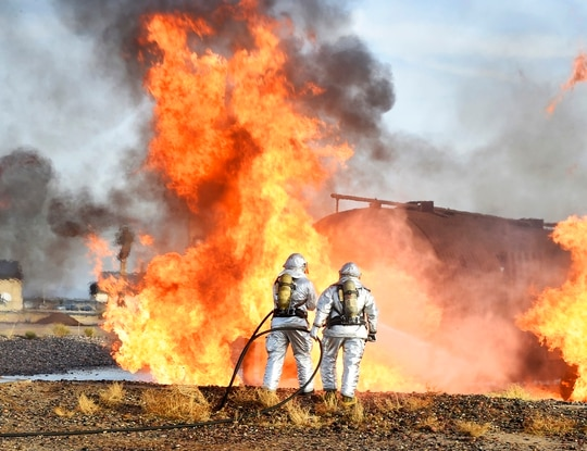 Firefighters with the 56th Civil Engineer Squadron and Gila Bend Fire Department spray water onto a fire during training Dec. 7, 2016, at Luke Air Force Base, Ariz. (Senior Airman James Hensley/Air Force)