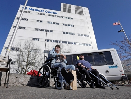 Veterans wait outside the Veterans Affairs Puget Sound Medical Center in Seattle on March 30, 2015. Department officials on Wednesday released new proposed standards for veterans seeking care at outside clinics and hospitals, at VA's expense. (Elaine Thompson/AP)