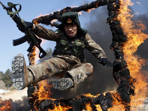 A Chinese soldier jumps through a ring of fire during a