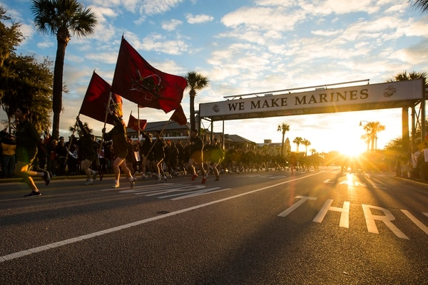 "New Marines of Golf Company, 2nd Recruit Training Battalion, and Papa Company, 4th Recruit Training Battalion, run under the iconic ""We Make Marines"" sign during a traditional motivational run through the streets of Parris Island, S.C., Feb. 25, 2016. (Lance Cpl. Aaron Bolser/Marine Corps)"