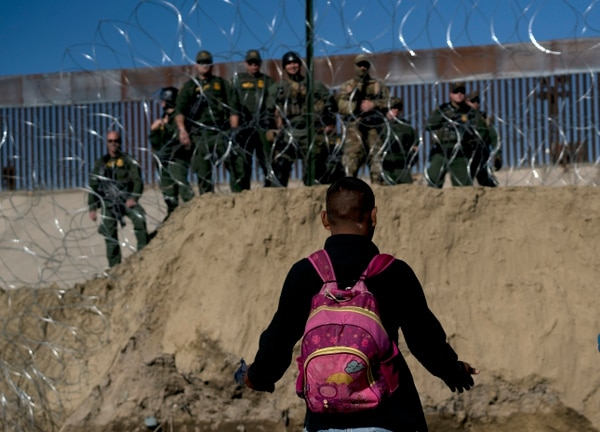 A Honduran migrant converses with U.S border agents on the other side of razor wire after they fired tear gas at migrants pressing to cross into the U.S. from Tijuana, Mexico, Sunday, Nov. 25, 2018. (Ramon Espinosa/Associated Press)