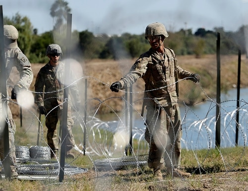 Troops install multiple tiers of concertina wire along the banks of the Rio Grande near the Juarez-Lincoln Bridge at the U.S.-Mexico border in Laredo, Texas. The Pentagon announced Thursday it would decrease its contribution of forces from 5,500 to 4,000. (Eric Gay/AP)