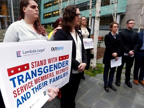 Plaintiffs in a court case stand with supporters at a federal courthouse in Seattle in March 2018. The Supreme Court ruled Tuesday, Jan. 22, 2019, that the Trump administration may move forward with a ban on transgender service members. (Elaine Thompson/AP)