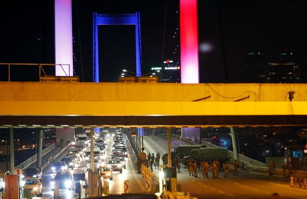 Turkish soldiers block Istanbul's iconic Bosporus Bridge on Friday, July 15, 2016, lit in the colours of the French flag in solidarity with the victims of Thursday's attack in Nice, France. A group within Turkey's military has engaged in what appeared to be an attempted coup, the prime minister said, with military jets flying over the capital and reports of vehicles blocking two major bridges in Istanbul. Prime Minister Binali Yildirim told NTV television: