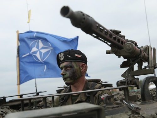 A soldier of the Polish Army sits in a tank as a NATO flag flies behind during the NATO Noble Jump military exercises of the VJTF forces on June 18, 2015 in Zagan, Poland. The VJTF, the Very High Readiness Joint Task Force, is NATO's response to Russia's annexation of Crimea and the conflict in eastern Ukraine. Troops from Germany, Norway, Belgium, Poland, Czech Republic, Lithuania and Belgium were among those taking part today. (Photo by Sean Gallup/Getty Images)