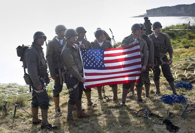 Rangers from the U.S. 75th Ranger Regiment, in period dress, hold the American flag after scaling the cliffs of Pointe-du-Hoc