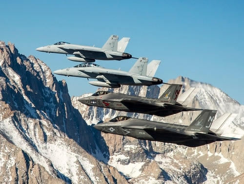 Two F-35C Lightning II aircraft fly in formation over the Sierra Nevada mountain range with to two F/A-18E/F Super Hornets from Naval Air Station Lemoore. Navy Strike Fighter Squadron 147 has begun the transition to becoming the Navy's first Joint Strike Fighter squadron. (Navy) (Lt. Cmdr. Darin Russell/Navy)