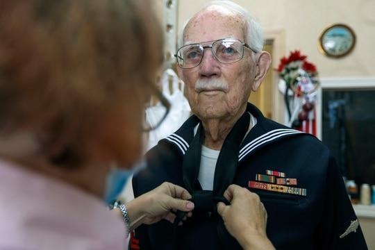 Joseph Hall, 96, of Dunedin, right, holds still as seamstress Susan Williams, 57, of Tarpon Springs, ties a knot into a tie Feb. 3, 2021, in Dunedin, Fla. (Chris Urso/Tampa Bay Times via AP)