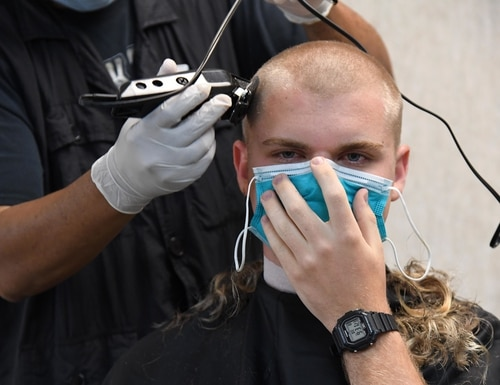 Julius Gines, AAFES barber, shaves the head of Airman Basic Ian Martin, 37th Training Wing, 737th Training Group Detachment 5 trainee, at Keesler Air Force Base, Mississippi, April 8, 2020. Nearly 60 Airmen completed the six-week basic military training course. In order to maximize resources, the Air Force sent new recruits to Keesler to demonstrate a proof of concept to generate the force at multiple locations during contingencies. (Kemberly Groue/Air Force)