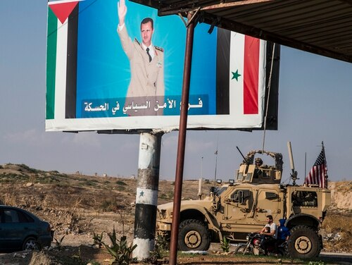 U.S. military convoy drives the he town of Qamishli, north Syria, by a poster showing Syrain President Bashar Aassad Saturday, Oct. 26. 2019. (Baderkhan Ahmad/AP)