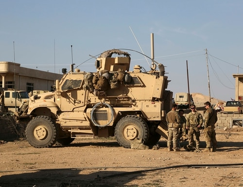 In this Feb. 23, 2017, photo, U.S. Army soldiers stand outside their armored vehicle on a joint base with Iraqi army south of Mosul, Iraq. (Khalid Mohammed/AP)