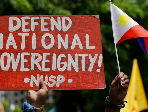 A protester holds a slogan during a rally outside the Chinese consulate in the financial district of Makati, metropolitan Manila, Philippines to mark Independence Day on Wednesday. (Aaron Favila/AP)