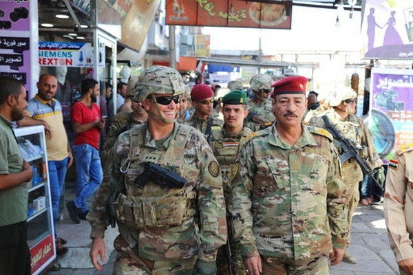 Lt. Gen. Paul Funk, left, commanding general of Combined Joint Task Force-Operation Inherent Resolve, and Iraqi Maj. Gen. Najm Abdullah al-Jibouri, right, commander of the Nineveh Liberation Operation, walk through a busy market near the University of Mosul on Oct. 4, 2017. (Spc. Avery Howard/Army via AP)
