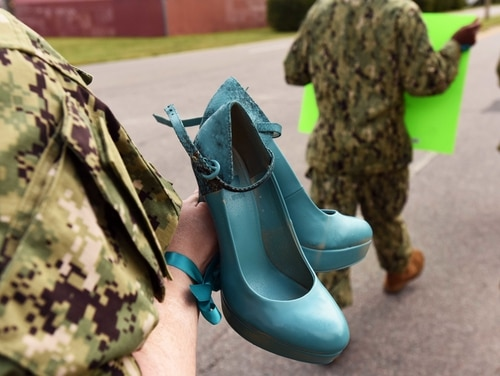 "A sailor from Navy Expeditionary Combat Command carries a pair of shoes, painted teal to symbolize victims of sexual assault, as she participates in the Aug. 25 ""Walk a Mile in Their Shoes"" command event at Joint Expeditionary Base Little Creek. (Mass Communication Specialist 3rd Class Lisa Reese/Navy)"