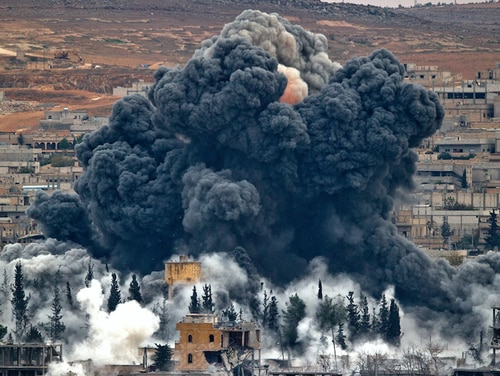 Smoke rises from the Syrian city of Kobani, in 2017, following an airstrike by the U.S.-led coalition. (Vadim Ghirda/AP)