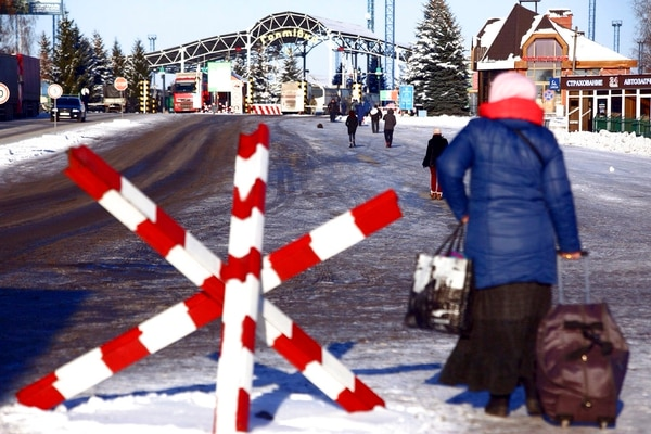 A woman walks to cross the checkpoint at the border with Russia in Hoptivka, Ukraine, on Friday. (Pavlo Pakhomenko/AP)