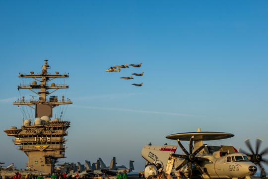 U.S. Navy F/A-18E and F Super Hornet fighter jets, an E-2C Hawkeye tactical airborne early warning aircraft and French Marine Nationale Dassault Rafale fighter jets fly in formation over the aircraft carrier Dwight D. Eisenhower. (MCSN Jacob Hilgendorf/Navy)